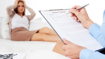 Close-up of psychologist filling out a report.