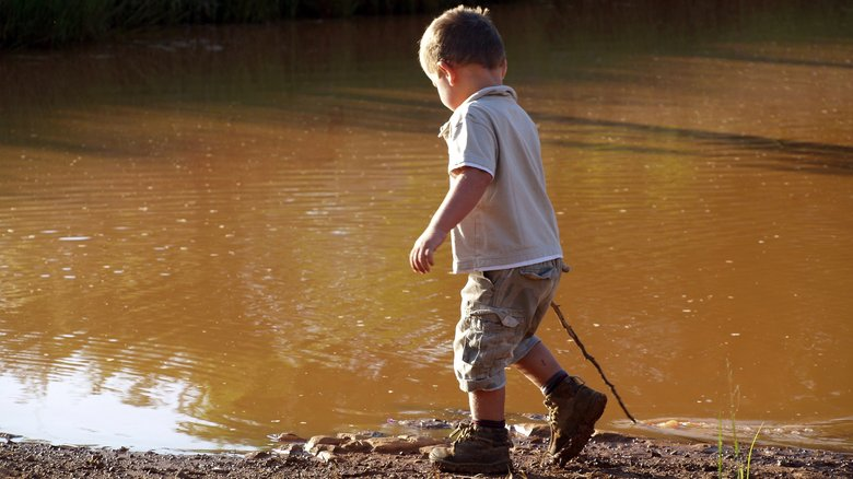 Child alone walking by a river.
