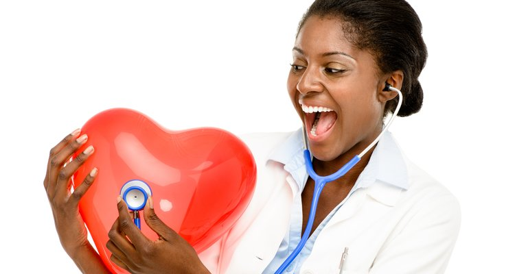 A nurse holding a red heart.