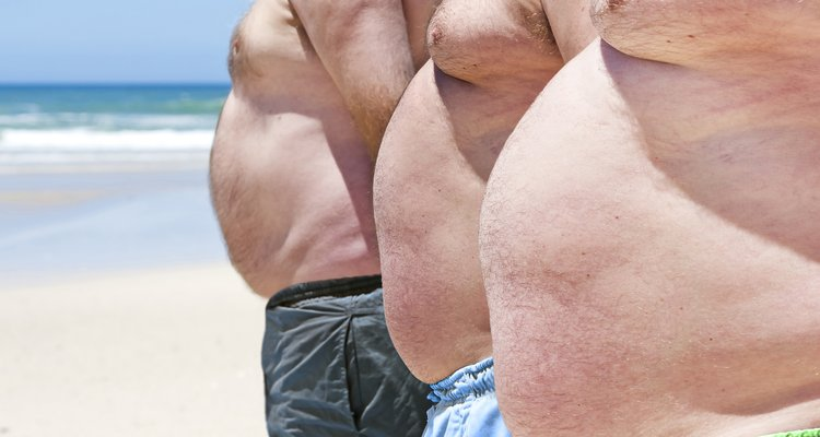 Close up of three obese fat men on the beach showing their unhealthy bellies.